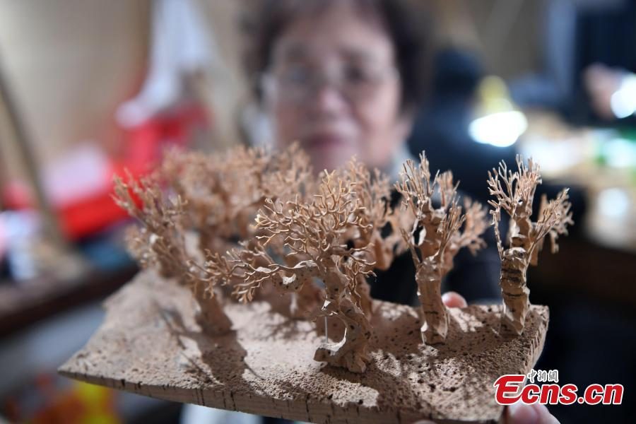 Folk artist Chen Xuerong, who has practiced the craft for 60 years, carves on bark at a workshop in Fuzhou City, East China\'s Fujian Province. As an intangible cultural heritage, bark carving is regarded as one of the three treasures of Fujian. Craftsmen can carve elaborate scenes, including pavilions, bridges and landscape features, onto the bark. The craft is in decline today as fewer young people are interested in the time-consuming profession. (Photo: China News Service/Zhang Bin)