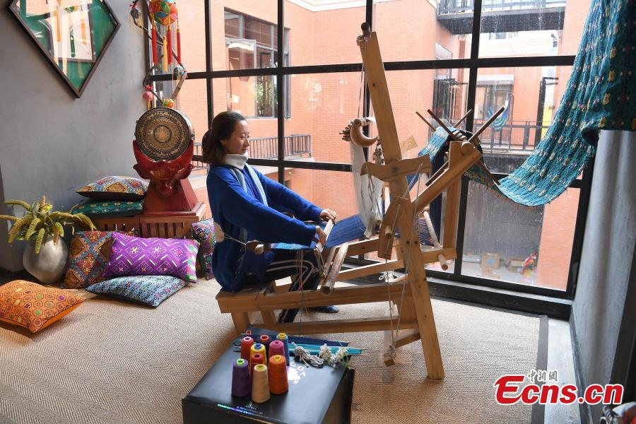 A store features products that integrate the intangible cultural heritages of the Zhuang people in Nanning City, Southwest China\'s Guangxi Zhuang Autonomous Region, Dec. 17, 2018. The products, including leatherware, clothes and bags, highlight the unique crafts of the Zhuang people. (Photo: China News Service/Yu Jing)
