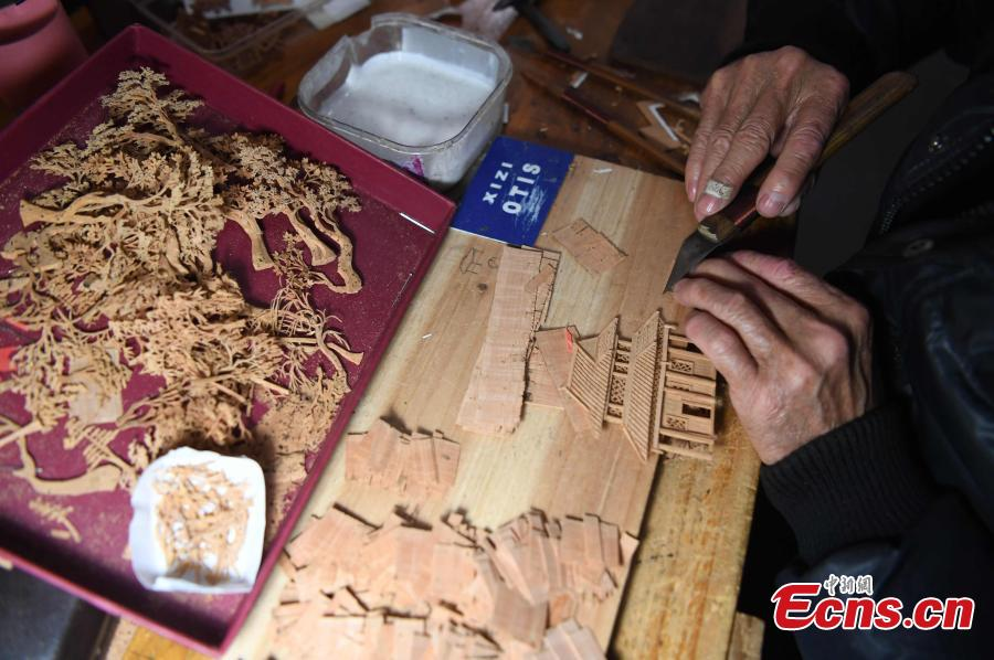 A craftsman carves on bark at a workshop in Fuzhou City, East China\'s Fujian Province. As an intangible cultural heritage, bark carving is regarded as one of the three treasures of Fujian. Craftsmen can carve elaborate scenes, including pavilions, bridges and landscape features, onto the bark. The craft is in decline today as fewer young people are interested in the time-consuming profession. (Photo: China News Service/Zhang Bin)