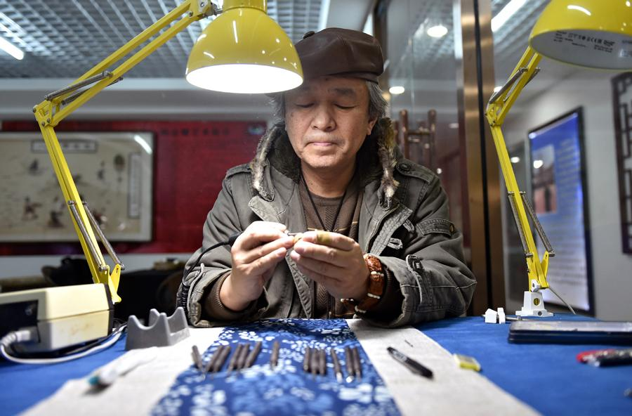 Han Zhiyao creates a nut carving work at his studio in Dalian, Liaoning Province, on Dec。 12. (Photo/Xinhua)