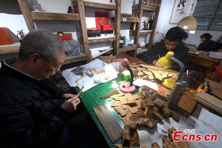 Craftsmen carve on bark at a workshop in Fuzhou City, East China\'s Fujian Province. As an intangible cultural heritage, bark carving is regarded as one of the three treasures of Fujian. Craftsmen can carve elaborate scenes, including pavilions, bridges and landscape features, onto the bark. The craft is in decline today as fewer young people are interested in the time-consuming profession. (Photo: China News Service/Zhang Bin)