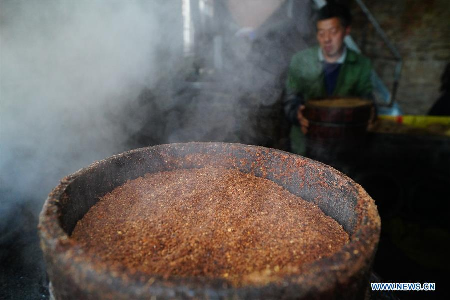 Villager Tan Han steams camellia seeds for oil extraction in Licha Village of Longsheng County, south China\'s Guangxi Zhuang Autonomous Region, Dec. 17, 2018. Camellia oil made with traditional methods by workshops in the village is quite popular in market because of its better quality and longer guarantee. (Xinhua/Huang Yongdan)