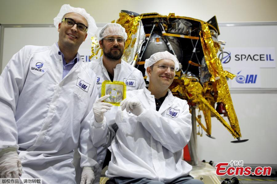 Members of Israeli non-profit group SpaceIL and representatives from Israel Aerospace Industries (IAI) hold a time capsule next to an unmanned spacecraft during a presentation to the media of the time capsule, intended to travel to the moon with the spacecraft in early 2019, at the clean room of IAI\'s space division in Yehud, Israel Dec. 17, 2018. (Photo/Agencies)