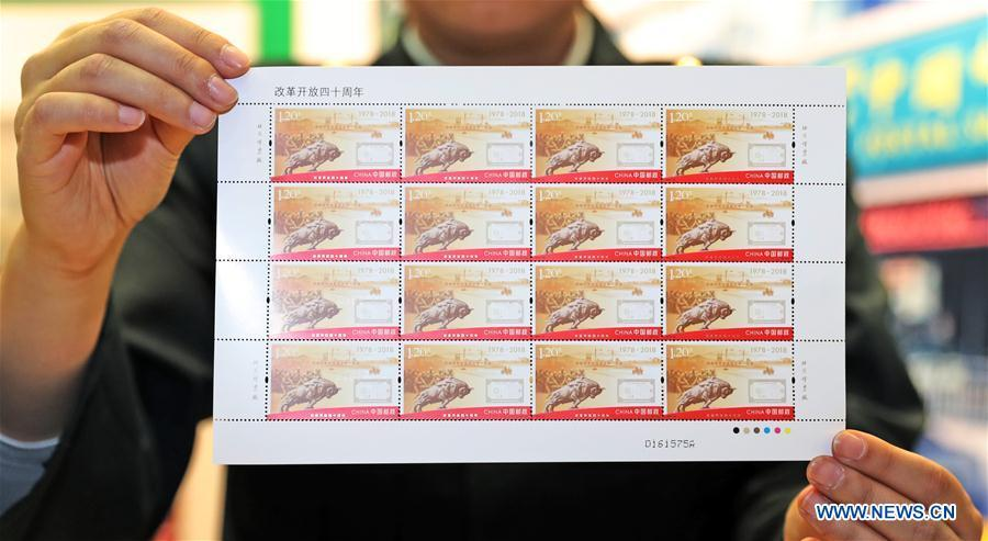 A staff member shows the commemorative stamps marking the 40th anniversary of China\'s reform and opening up at the post office of Liaoning provincial archives in Shenyang, capital of northeast China\'s Liaoning Province, Dec. 18, 2018. China Post released a set of commemorative stamps and one souvenir sheet marking the 40th anniversary of China\'s reform and opening up on Tuesday. (Xinhua/Yang Qing)