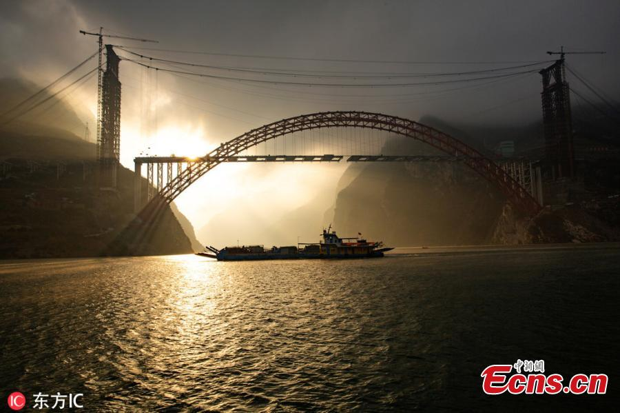 Sunrise at the construction site of a bridge over the Yangtze River in Zigui County, Central China\'s Hubei Province. The confluence of Xiangxi Stream, a tributary of China\'s greatest river, and Xiling Gorge, one of the Three Gorges, is a tourist attraction renowned for its magnificent scenic beauty. (Photo/IC)