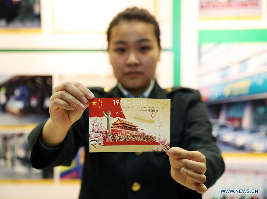 A staff member shows the souvenir sheet marking the 40th anniversary of China\'s reform and opening up at the post office of Liaoning provincial archives in Shenyang, capital of northeast China\'s Liaoning Province, Dec. 18, 2018. China Post released a set of commemorative stamps and one souvenir sheet marking the 40th anniversary of China\'s reform and opening up on Tuesday. (Xinhua/Yang Qing)