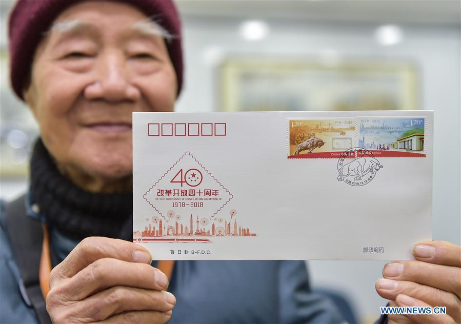 Chang Rongguang, an 82-year-old stamp collector, shows the first day cover with stamps released to mark the 40th anniversary of China\'s reform and opening up at a post office in Xicheng District of Beijing, capital of China, Dec. 18, 2018. China Post released a set of commemorative stamps and one souvenir sheet marking the 40th anniversary of China\'s reform and opening up on Tuesday. (Xinhua/Li He)