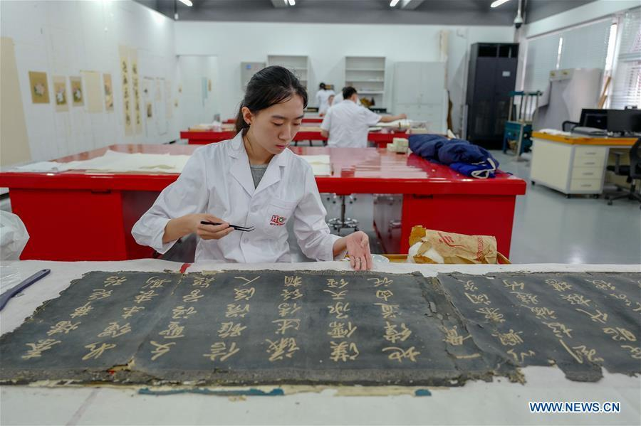 A staff worker repairs a calligraphy collection at a hospital for conservation in the Palace Museum in Beijing, capital of China, June 9, 2018. (Xinhua/Liu Chan)