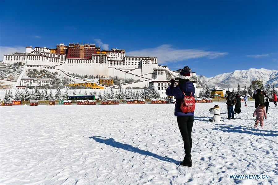 A tourist takes photos at the snow-covered Potala Palace square in Lhasa, capital of southwest China\'s Tibet Autonomous Region, Dec. 19, 2018. Lhasa witnessed the first snow this winter on Tuesday. (Xinhua/Liu Dongjun)