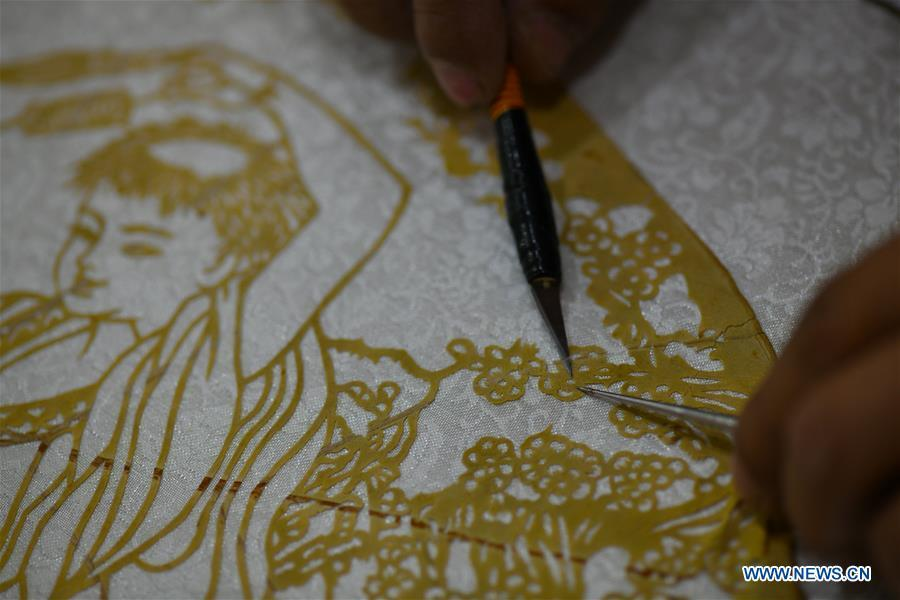 Niu Shimin creates a paper cutting work with leaves at his workshop in Wuji County, north China\'s Hebei Province, Dec. 19, 2018. Niu Shimin has been interested in paper cutting since he was young. He created his own style through over 30 years of practicing and was awarded as the inheritor of this provincial intangible cultural heritage in 2008. (Xinhua/Chen Qibao)