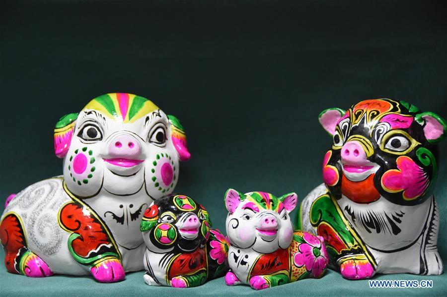 Photo taken on Dec. 20, 2018 shows clay pig sculptures designed by master Hu Xinming in Liuying Village of Fengxiang County, northwest China\'s Shaanxi Province. Artists of Liuying Village of Fengxiang County, known as the hometown of clay sculpture, were busy making clay sculptures to greet the upcoming Chinese lunar new year, the Year of the Pig. (Xinhua/Du Honggang)