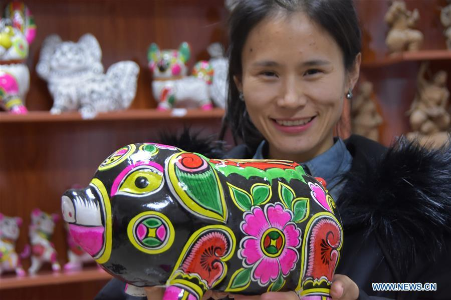 A clay sculpture artist shows a clay pig sculpture in Liuying Village of Fengxiang County, northwest China\'s Shaanxi Province, Dec. 20, 2018. Artists of Liuying Village of Fengxiang County, known as the hometown of clay sculpture, were busy making clay sculptures to greet the upcoming Chinese lunar new year, the Year of the Pig. (Xinhua/Du Honggang)