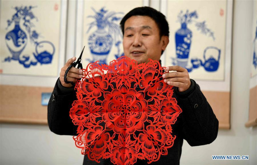 Niu Shimin displays his work of paper cutting at his workshop in Wuji County, north China\'s Hebei Province, Dec. 19, 2018. Niu Shimin has been interested in paper cutting since he was young. He created his own style through over 30 years of practicing and was awarded as the inheritor of this provincial intangible cultural heritage in 2008. (Xinhua/Chen Qibao)