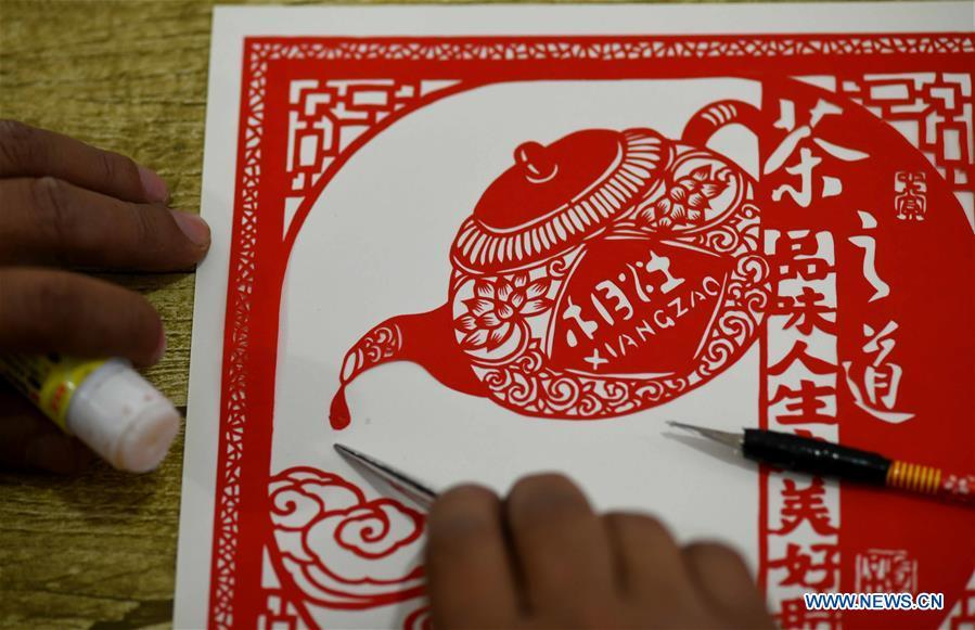 Niu Shimin creates a paper cutting work at his workshop in Wuji County, north China\'s Hebei Province, Dec. 19, 2018. Niu Shimin has been interested in paper cutting since he was young. He created his own style through over 30 years of practicing and was awarded as the inheritor of this provincial intangible cultural heritage in 2008. (Xinhua/Chen Qibao)