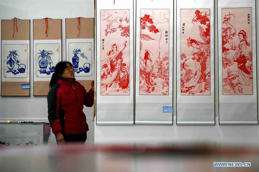 A visitor looks at Niu Shimin\'s works of paper cutting at the workshop in Wuji County, north China\'s Hebei Province, Dec. 19, 2018. Niu Shimin has been interested in paper cutting since he was young. He created his own style through over 30 years of practicing and was awarded as the inheritor of this provincial intangible cultural heritage in 2008. (Xinhua/Chen Qibao)