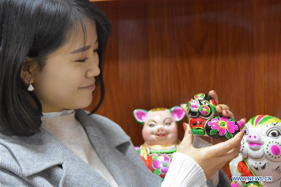 A visitor looks at a clay pig sculpture in Liuying Village of Fengxiang County, northwest China\'s Shaanxi Province, Dec. 20, 2018. Artists of Liuying Village of Fengxiang County, known as the hometown of clay sculpture, were busy making clay sculptures to greet the upcoming Chinese lunar new year, the Year of the Pig. (Xinhua/Du Honggang)