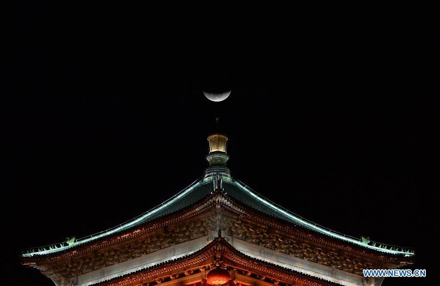 Photo taken on Jan. 31, 2018 shows a moon on the top of the Bell Tower in Xi\'an, capital city of northwest China\'s Shaanxi Province. The living and working scenes of Chinese people in the past year have created a series of amazing views, some of which formed geometric figures. Those photos tell the development and progress of the country in 2018. (Xinhua/Li Yibo)