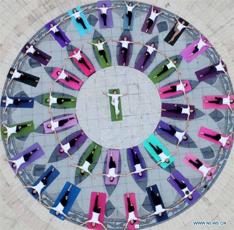 People take part in a yoga practice at the Baihua Park in Xiajiang County, east China\'s Jiangxi Province, June 21, 2018. The living and working scenes of Chinese people in the past year have created a series of amazing views, some of which formed geometric figures. Those photos tell the development and progress of the country in 2018. (Xinhua/Chen Fuping)