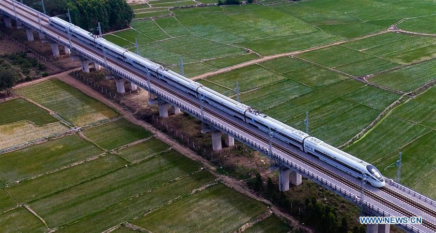 Photo taken on March 7, 2018 shows a bullet train running on the western track of the high-speed loop line in Changjiang Li Autonomous County, south China\'s Hainan Province. The living and working scenes of Chinese people in the past year have created a series of amazing views, some of which formed geometric figures. Those photos tell the development and progress of the country in 2018. (Xinhua/Yang Guanyu)