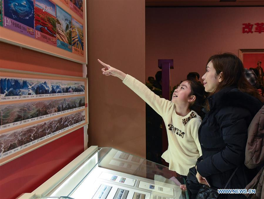 People look at the stamps displayed during a major exhibition to commemorate the 40th anniversary of China\'s reform and opening-up at the National Museum of China in Beijing, capital of China, Dec. 22, 2018. The exhibition has received more than 1.85 million visitors since its opening. (Xinhua/Li He)