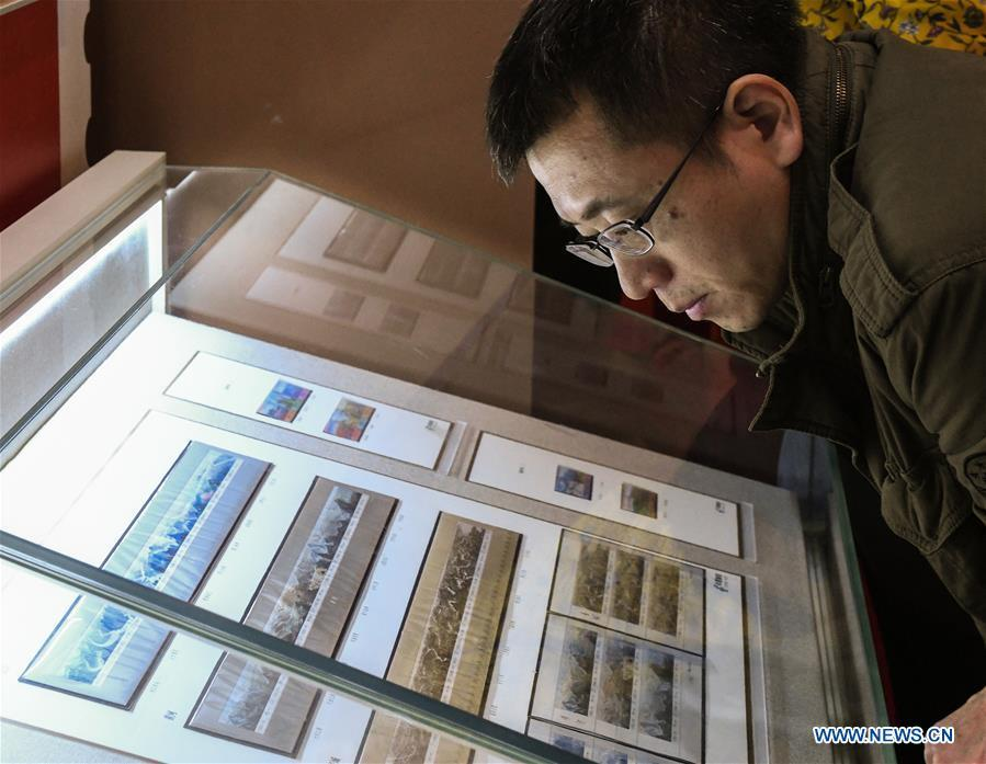 A man looks at the stamps displayed during a major exhibition to commemorate the 40th anniversary of China\'s reform and opening-up at the National Museum of China in Beijing, capital of China, Dec. 22, 2018. The exhibition has received more than 1.85 million visitors since its opening. (Xinhua/Li He)