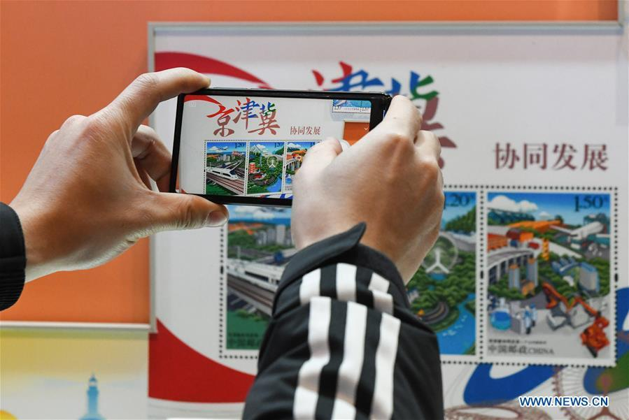 A visitor takes photos of the stamps displayed during a major exhibition to commemorate the 40th anniversary of China\'s reform and opening-up at the National Museum of China in Beijing, capital of China, Dec. 22, 2018. The exhibition has received more than 1.85 million visitors since its opening. (Xinhua/Li He)