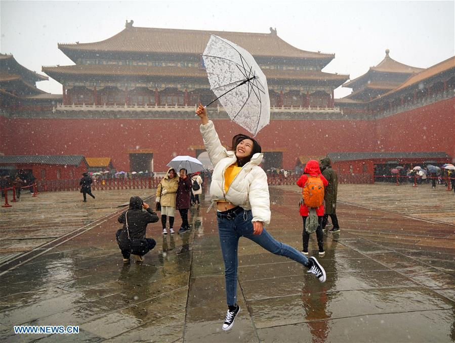 A tourist poses for photos in snow at the Palace Museum in Beijing, capital of China, March 17, 2018. The Palace Museum, or the former imperial palace in downtown Beijing, will open 85 percent of its areas to the public, compared with the current 80 percent, the China Daily reported Friday. Most of the areas inside the museum, also known as the Forbidden City, will no longer be off-limits for the public, the newspaper quoted Shan Jixiang, the museum\'s curator, as saying. The biggest of its kind in the world, the Forbidden City is gradually opening more of its coverage of 720,000 square meters to visitors in recent years. Only 30 percent of its areas were accessible by the public in 2012. Some rooms that had not been opened for decades were used as \