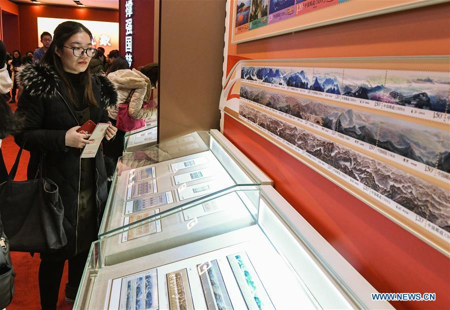 A woman looks at the stamps displayed during a major exhibition to commemorate the 40th anniversary of China\'s reform and opening-up at the National Museum of China in Beijing, capital of China, Dec. 22, 2018. The exhibition has received more than 1.85 million visitors since its opening. (Xinhua/Li He)