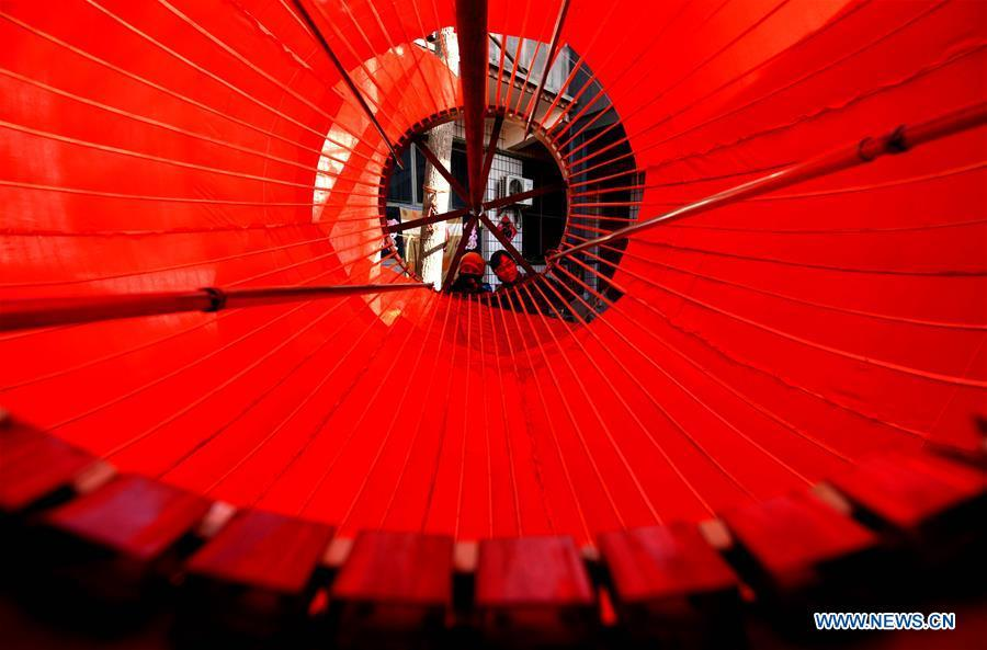 Workers make a big red lantern in Tuntou Village, Gaocheng District, Shijiazhuang City, north China\'s Hebei Province, Dec. 23, 2018. As the New Year approaches, lantern craftsmen in Gaocheng, which is known for its lantern manufacturing, are busy making red lanterns. (Xinhua/Chen Qibao)