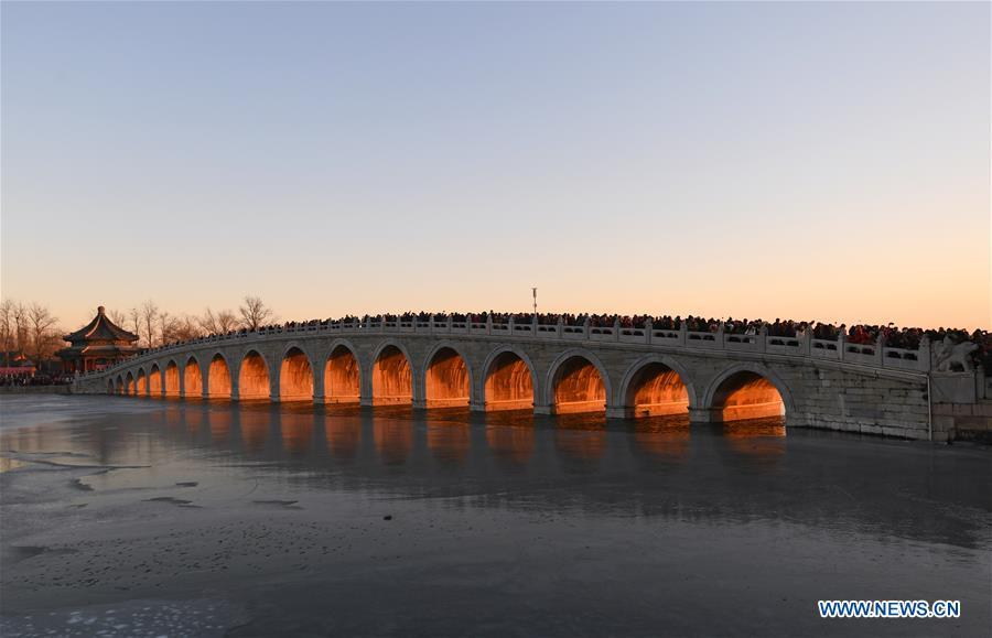 The Qikong Bridge with sunset glow shining through its holes is seen at the Summer Palace in Beijing, capital of China, Dec, 23, 2018. (Xinhua/Chen Yehua)