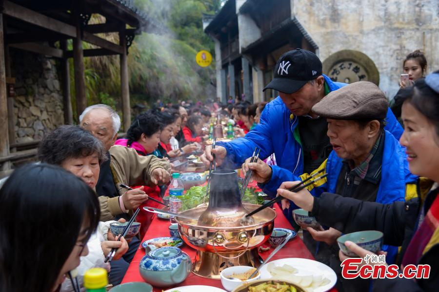 A hot-pot banquet is held on a street in Huangling Ancient Village in Wuyuan County, East China\'s Jiangxi Province, Dec. 22, 2018. The centerpiece of the long-table banquet, a traditional manner in which to celebrate some major festivals and entertain guests, is a giant copper pot measuring three meters in height and two meters in diameter. Visitors, including some from Singapore and Malaysia, joined the feast, where the tables extended for 100 meters. (Photo: China News Service/Fang Huabin)