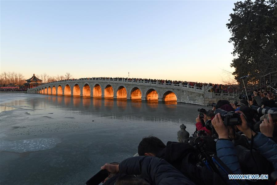 Visitors and photographers take photos of the Qikong Bridge with sunset glow shining through its holes at the Summer Palace in Beijing, capital of China, Dec, 23, 2018. (Xinhua/Chen Yehua)