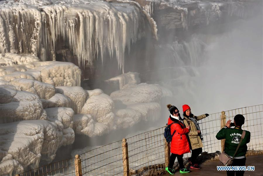 Tourists take photos of icicles of the Hukou Waterfall of the Yellow River in Jixian County, north China\'s Shanxi Province, Dec. 23, 2018. (Xinhua/Lyu Guiming)