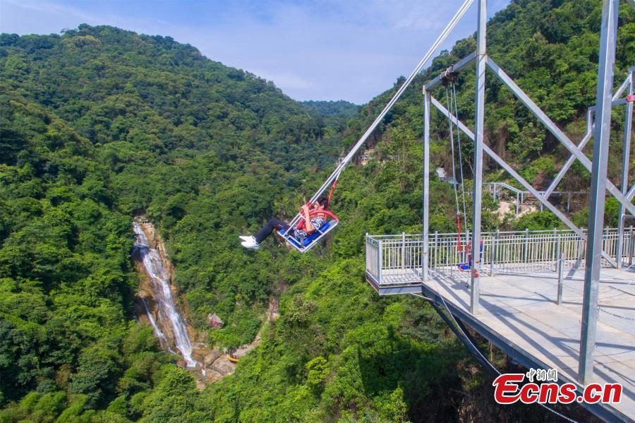 Photo shows a tourist experiencing the cliff swing that officially opened to the public in Qingyuan, Guangdong Province on December 19, 2018. The swing above a 198-meter waterfall on Mount Tianzi in Qingyuan, South China\'s Guangdong Province officially opens on Thursday after a four-month trial operation.  (Photo: China News Service/Cheng Jingwei)