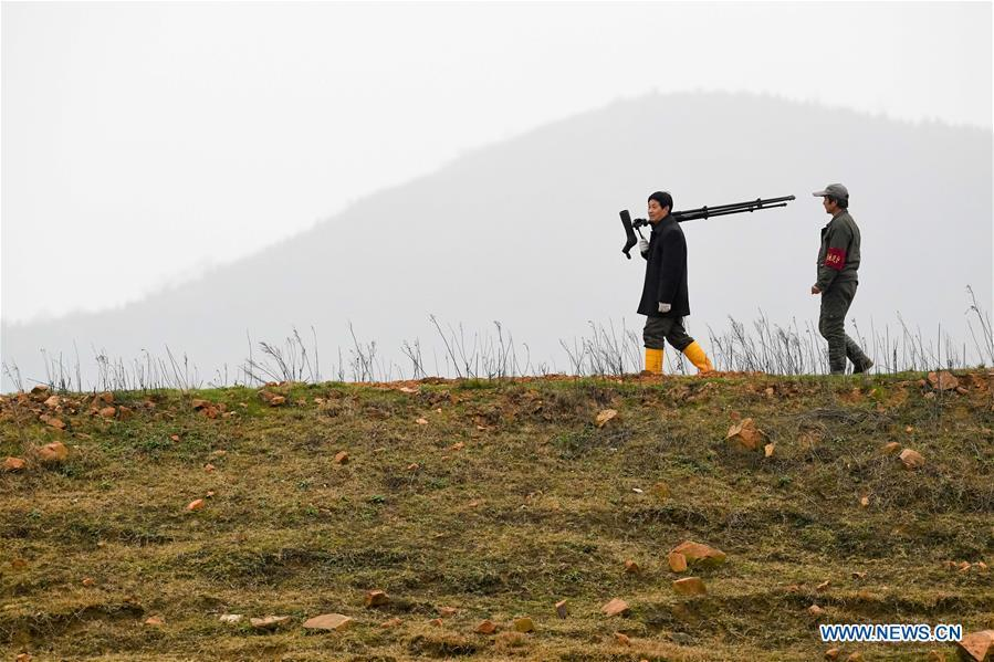 Wang Sanyi (L) patrols for migrant-bird protection in Caizi Lake wetland, Anqing, in east China\'s Anhui Province, Dec. 22, 2018. Wang Sanyi, 69, founded the Caizi Lake wetland ecological protection association with more than 300 members in 2010. Some villagers who used to be hunters now join the association, becoming volunteers to protect migrant birds. With the help of the association, the ecological environment of Caizi Lake wetland has been improved in recent years. Thanks to the efforts of protection, more and more migrant birds are seen here overwintering. \