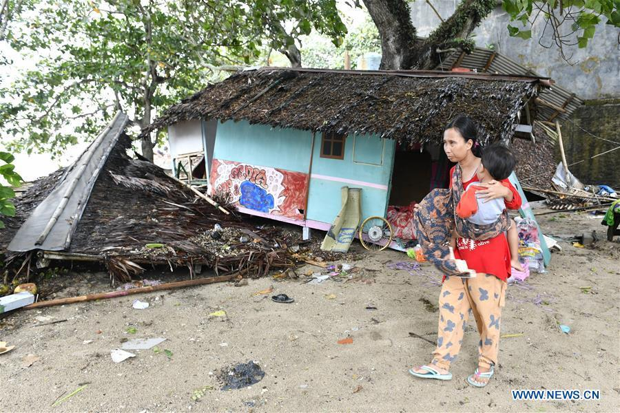 A woman holding her child walks by debris of a kiosk near the beach in Carita after a tsunami hit Sunda Strait in Pandeglang, Banten province, in Indonesia, Dec. 23, 2018. The total casualty of a tsunami triggered by the eruption of Krakatau Child volcano has increased to 222 people in coastal areas of Sunda Strait of western Indonesia, disaster agency official said here on Sunday. The catastrophe killed at least 222 people, wounded at least 843 ones and collapsed a total of 556 houses and nine hotels, and caused damages to scores of ships. (Xinhua/Veri Sanovri)