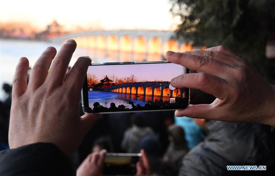 A visitor takes photos of the Qikong Bridge with sunset glow shining through its holes at the Summer Palace in Beijing, capital of China, Dec, 23, 2018. (Xinhua/Chen Yehua)