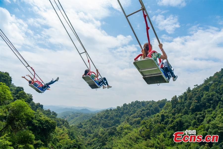 Photo shows three people up in the sky in the chair of a cliff swing that opened to the public in Qingyuan, Guangdong Province on December 19, 2018. The swing above a 198-meter waterfall on Mount Tianzi in Qingyuan, South China\'s Guangdong Province officially opens on Thursday after a four-month trial operation.  (Photo: China News Service/Cheng Jingwei)