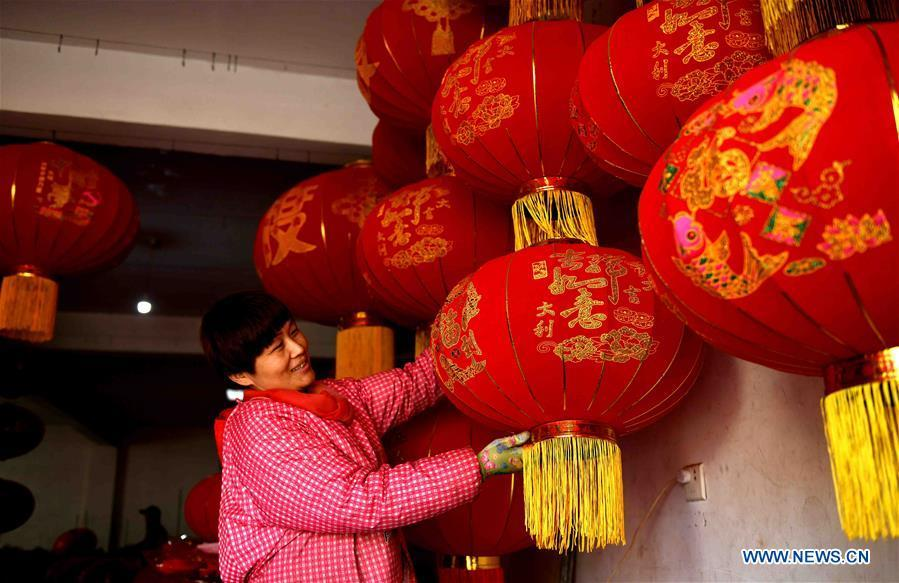A worker shows red lanterns in Tuntou Village, Gaocheng District, Shijiazhuang City, north China\'s Hebei Province, Dec. 23, 2018. As the New Year approaches, lantern craftsmen in Gaocheng, which is known for its lantern manufacturing, are busy making red lanterns. (Xinhua/Chen Qibao)