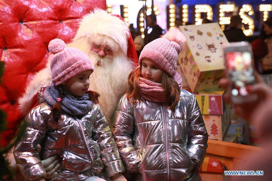 Two little girls pose for photos with a person in Santa Claus costume at Bucharest Winter Market at University Square, in Bucharest, Romania, on Dec. 24, 2018. (Xinhua/Gabriel Petrescu)