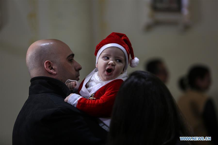 A baby in Santa Claus costume attends a Christmas mass at the Der Latin Church in Gaza City, on Dec. 24, 2018. (Xinhua/Stringer)