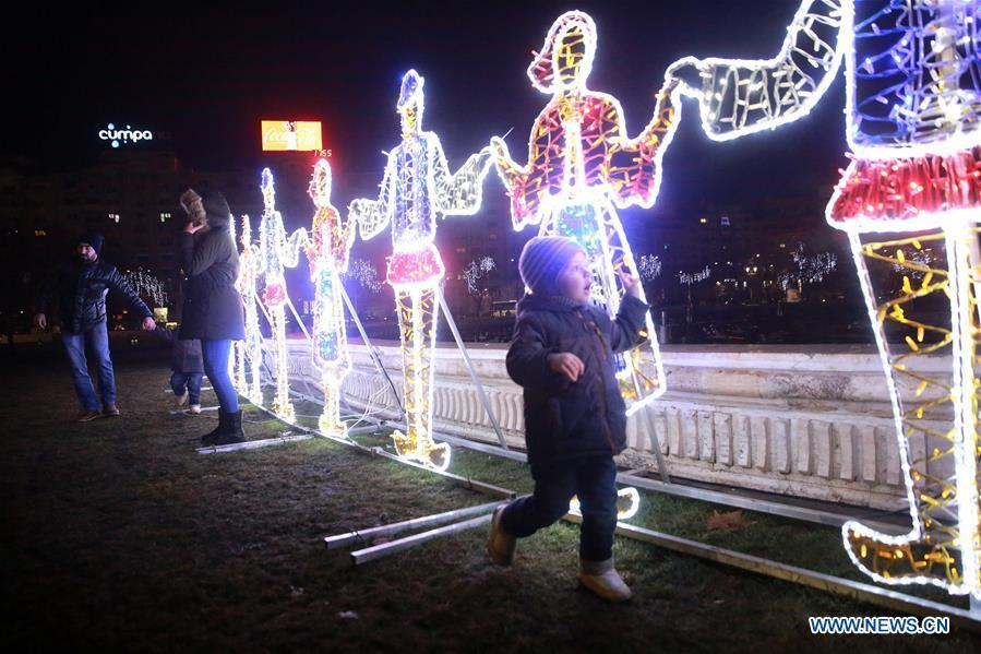 Light installations representing people in traditional costumes dancing Hora of Unity are seen in downtown Bucharest, Romania, on Dec. 24, 2018. (Xinhua/Gabriel Petrescu)
