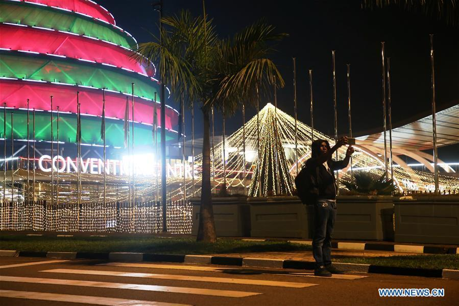 A person poses for a selfie with Christmas light decorations in Kigali, capital of Rwanda, on Dec. 24, 2018. (Xinhua/Lyu Tianran)