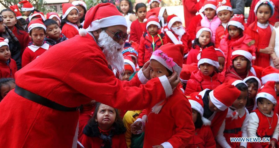 A Nepalese teacher dressed up as Santa Claus participates in celebration of Christmas at a local school in Kathmandu, Nepal, on Dec. 24, 2018. (Xinhua/Sunil Sharma)