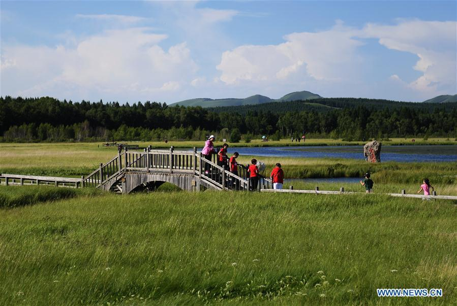 Photo taken on July 11, 2017 shows tourists visiting the Qixing Lake Scenic Area of the Saihanba State Forest Park in Chengde City, north China\'s Hebei Province. Saihanba is a vast forest covering nearly 75,000 hectares. It was a piece of barren land 55 years ago, but decades of hard afforestation efforts turned it into an important ecological shield for Beijing and Tianjin. China has seen reduced desertification and increased forest coverage since 1978, thanks to the Three-North Afforestation Program (TNAP), said a report released on Dec. 24, 2018. Constructed in the northeast, north and northwest China, TNAP is a national program fighting against soil erosion and wind-sand damage by planting sand-fixing forests. The area of sand-fixing forests has increased by 154 percent in the past 40 years, contributing to the reduction of desertification by around 15 percent, according to a report jointly released by the National Forestry and Grassland Administration (NFGA) and the Chinese Academy of Sciences. Over the past 40 years, TNAP increased the forest area by 30.14 million hectares and raised the forest coverage rate from 5.05 percent to 13.57 percent in the regions it covers, said Liu Dongsheng, deputy head of the NFGA. (Xinhua/Wang Xiao)