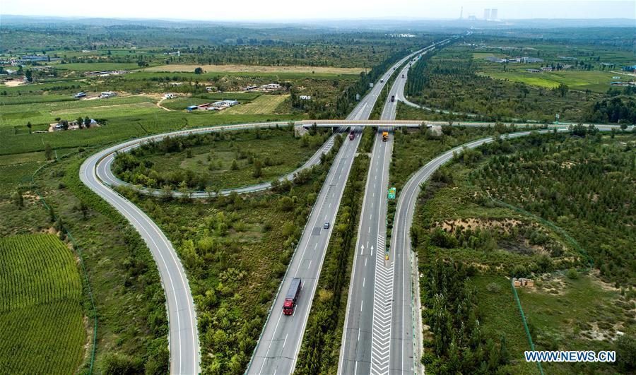 Vehicles run on the Yulin-Jingbian Expressway which runs through the Maowusu Desert, northwest China\'s Shaanxi Province, Aug. 1, 2018. The expressway is the first of the kind built in a desert in China. China has seen reduced desertification and increased forest coverage since 1978, thanks to the Three-North Afforestation Program (TNAP), said a report released on Dec. 24, 2018. Constructed in the northeast, north and northwest China, TNAP is a national program fighting against soil erosion and wind-sand damage by planting sand-fixing forests. The area of sand-fixing forests has increased by 154 percent in the past 40 years, contributing to the reduction of desertification by around 15 percent, according to a report jointly released by the National Forestry and Grassland Administration (NFGA) and the Chinese Academy of Sciences. Over the past 40 years, TNAP increased the forest area by 30.14 million hectares and raised the forest coverage rate from 5.05 percent to 13.57 percent in the regions it covers, said Liu Dongsheng, deputy head of the NFGA. (Xinhua/Tao Ming)