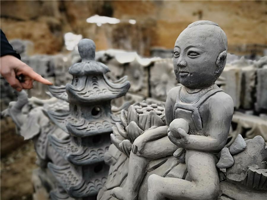 Liu Quan shows one of his works. (Photo by Wei Jianjun for chinadaily.com.cn)