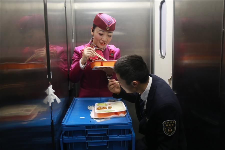 Liu Yuting and an intern conductor take time to eat lunch during a stop.  (Photo provided to chinadaily.com.cn)