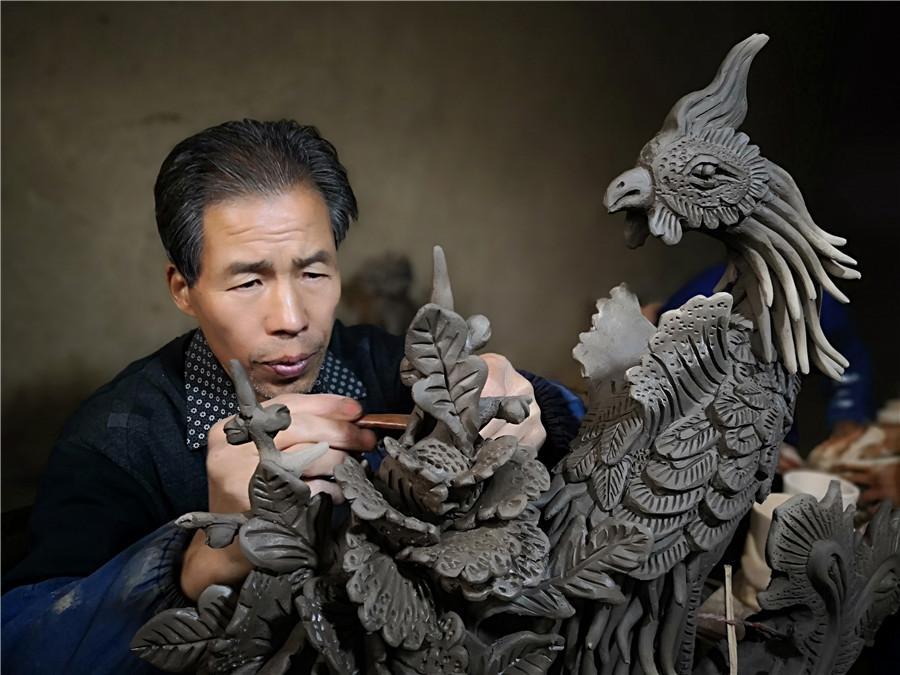 Liu Quan carves a phoenix, a bird from traditional Chinese myths.  (Photo by Wei Jianjun for chinadaily.com.cn)