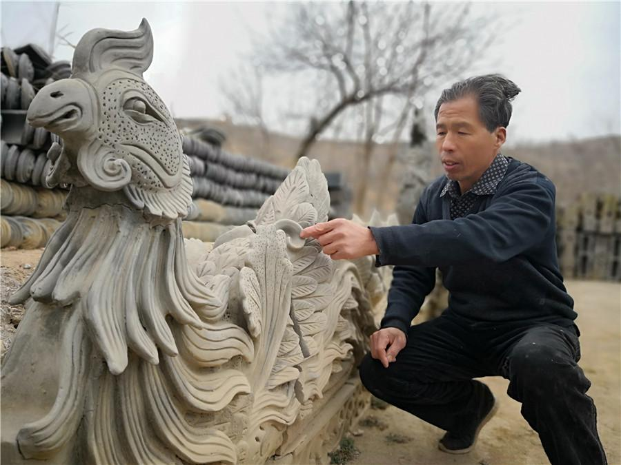 Liu Quan with one of his sculptures. He\'s a fourth-generation sculptor from the city of Pingliang in Northwest China\'s Gansu Province. (Photo by Wei Jianjun for chinadaily.com.cn)  Liu Quan, 55, is a fourth-generation sculptor from the city of Pingliang in Northwest China\'s Gansu Province.  Using mostly clay, his creations include figures, dragons, phoenixes and other imaginary beasts from traditional Chinese myths, as well as flora sculptures.  His family has been passing on the craft for over 200 years, while Liu himself has been devoted to the art since childhood, learning the techniques from previous generations.